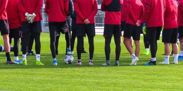 サッカーのトレーニングで選手たちが指導者中心に囲みながら会話を聞いている風景