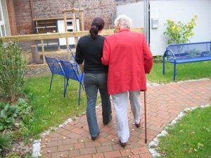 杖をついた高齢者に寄り添う介助者が2人で歩いている風景