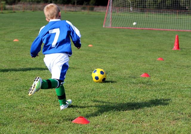 マーカーやパイロンを使ってサッカーのトレーニングをする少年